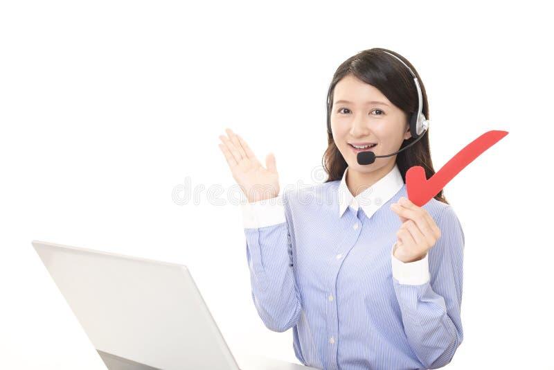 Call center operator with a check mark. Portrait of a call center operator stock image