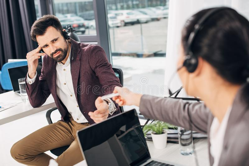 Call center operator giving medicine to coworker with headache stock photos