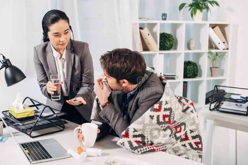 Call center operator giving pills and glass of water to sick coworker with cup stock photos