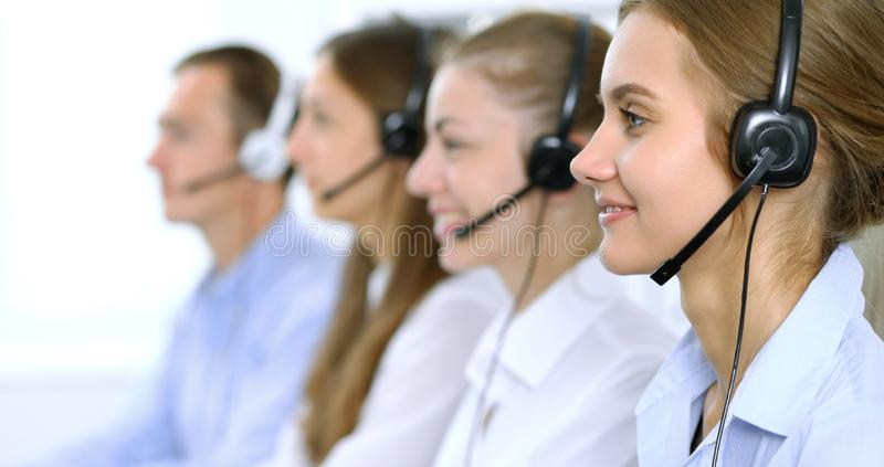 Call center operator in headset while consulting client. Telemarketing or phone sales.  stock photo