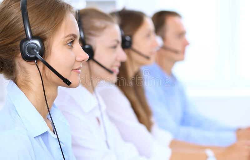 Call center operator in headset while consulting client. Telemarketing or phone sales.  royalty free stock images