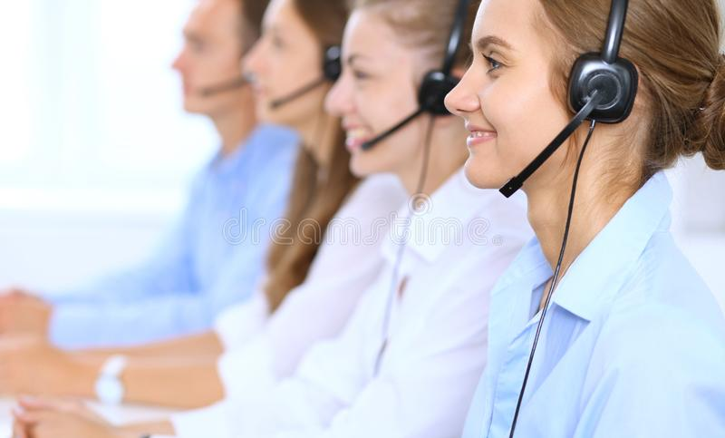 Call center operator in headset while consulting client. Telemarketing or phone sales.  stock photos