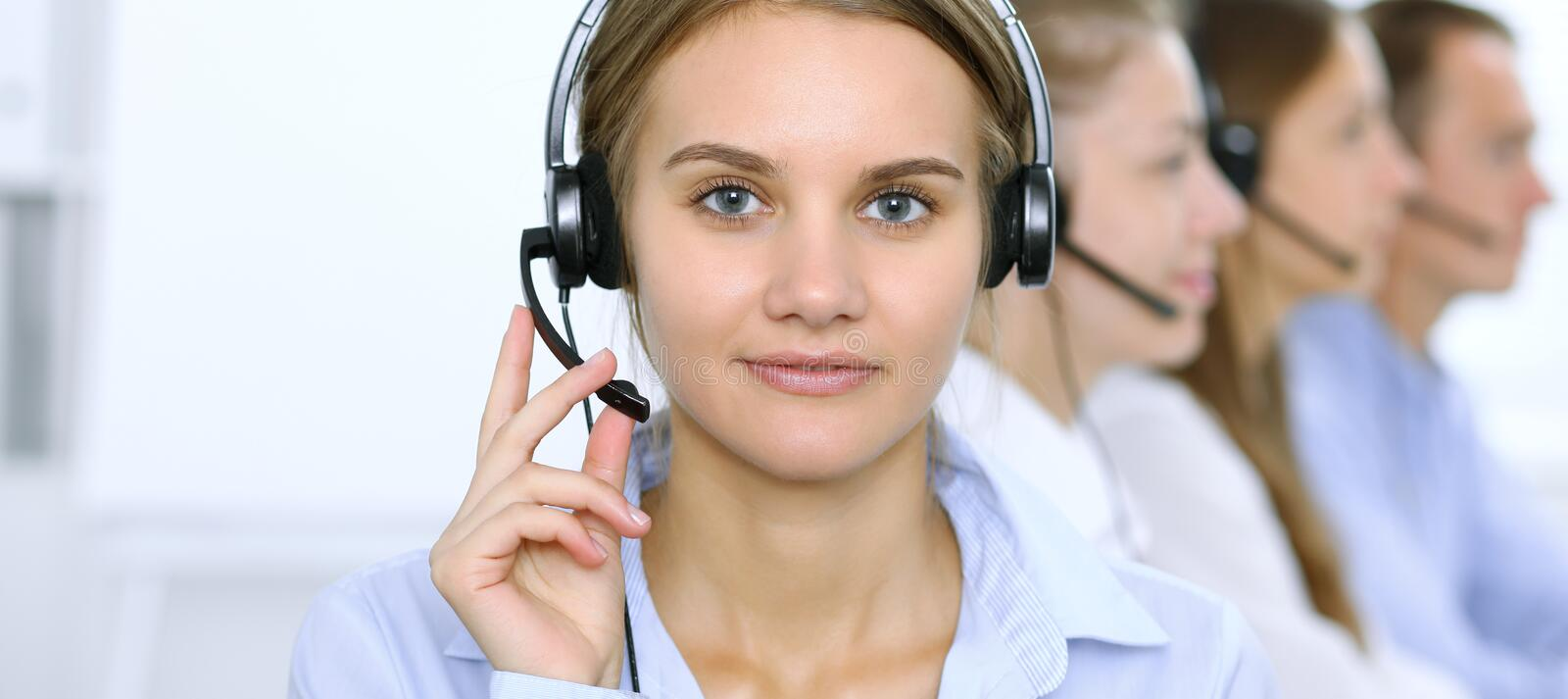 Call center operator in headset while consulting client. Telemarketing or phone sales.  stock image