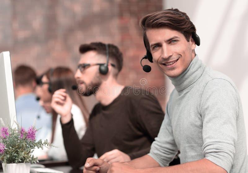 Call center operator sitting at his Desk. stock photos