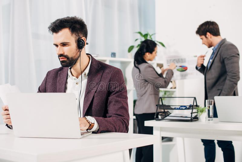 Call center operator working at laptop with coworkers on background royalty free stock images