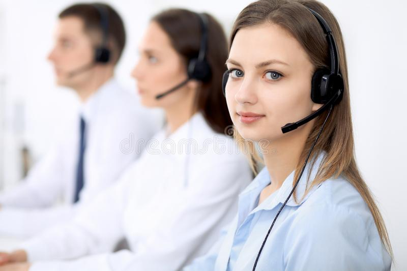 Call center operators. Focus on young cheerful smiling woman in headset. Business and customer service concepts royalty free stock photos