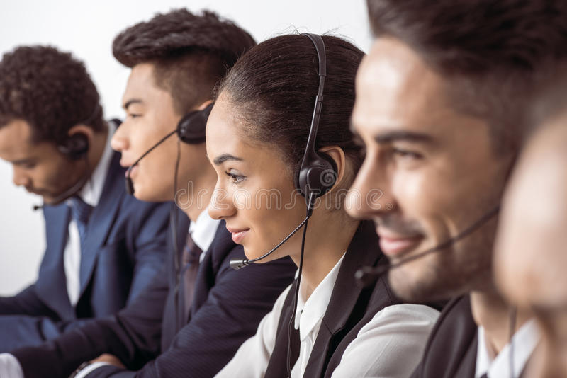 Call center operators in headsets working together. Close-up view of call center operators in headsets working together royalty free stock photos
