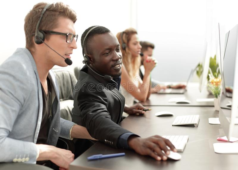 Call center operators sitting at their Desk. stock photography