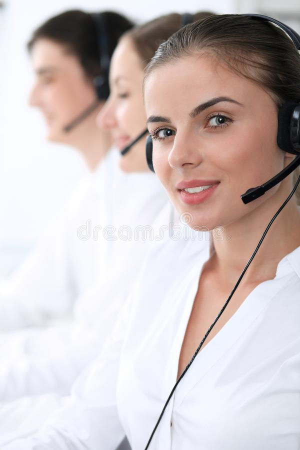 Call center operators at work. Focus at beautiful business woman in headset royalty free stock image