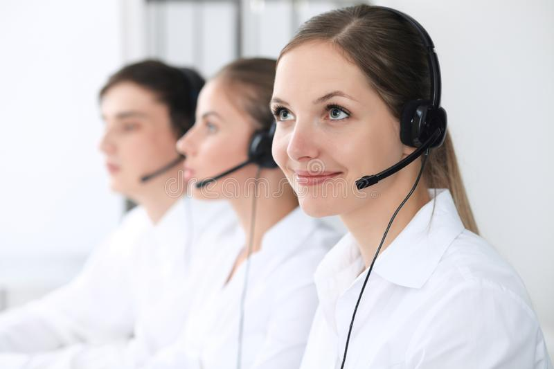 Call center operators at work. Focus at beautiful business woman in headset royalty free stock images