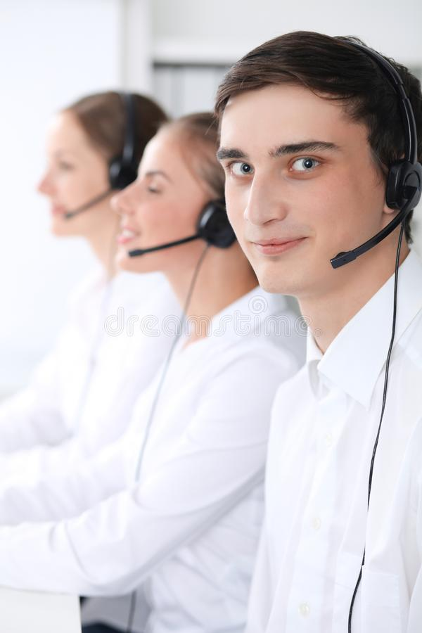 Call center operators at work. Focus at young man in headset stock photo