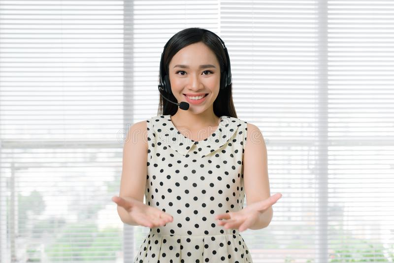 Call center operators. Young beautiful asian woman in headset stock images