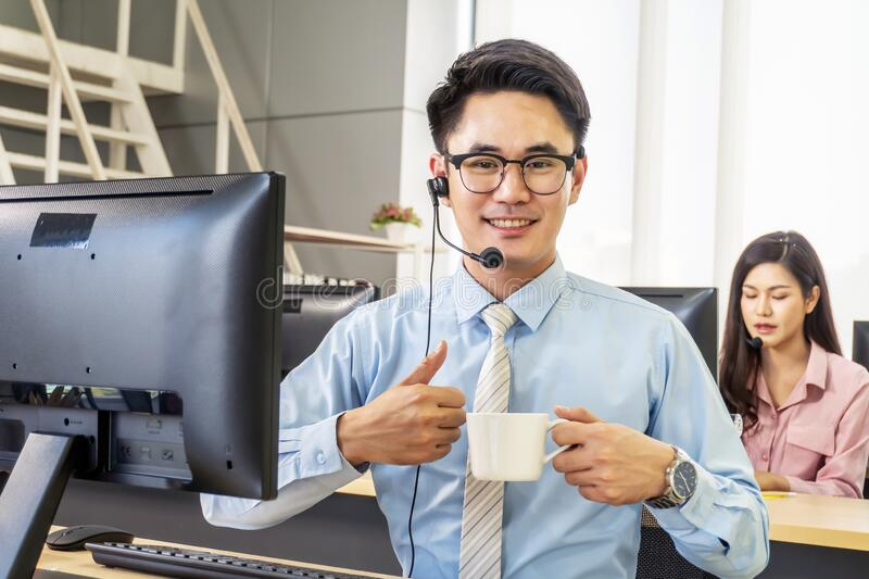 Male customer support phone operator at workplace, Cheerful call center man working from office talking with customer and drinking stock photography