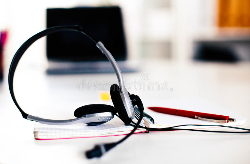 Call center service operator empty working place. Headset, glasses, keyboard and monitor at helpdesk employee workplace. Effective and efficient business stock photo