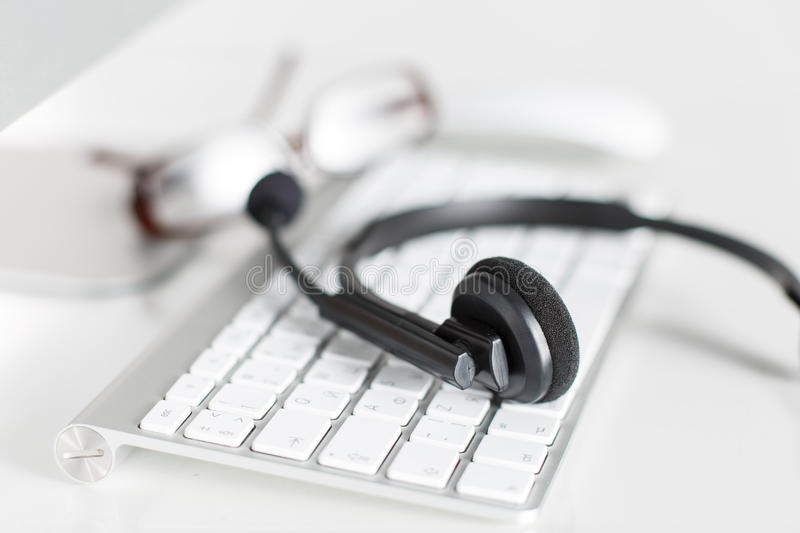 Call center service operator's empty working place. Headset, glasses, keyboard and monitor at helpdesk employee workplace. Effective and efficient business stock images