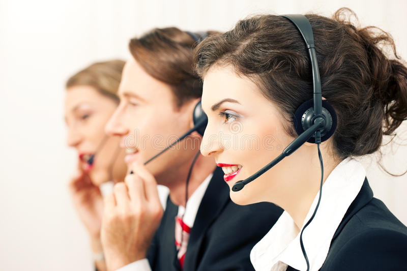 Call center team. Group of three customer care representatives in a call center with headphones