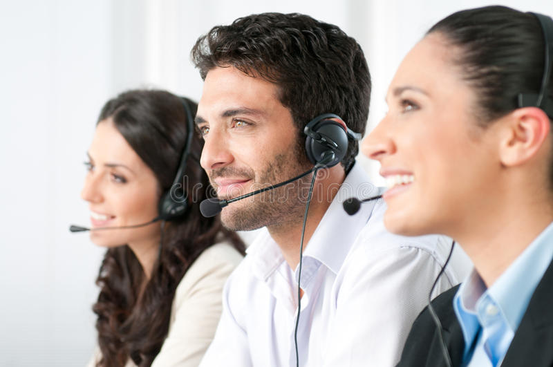 Call center team. Smiling positive young man with headset and colleagues in a modern call center office