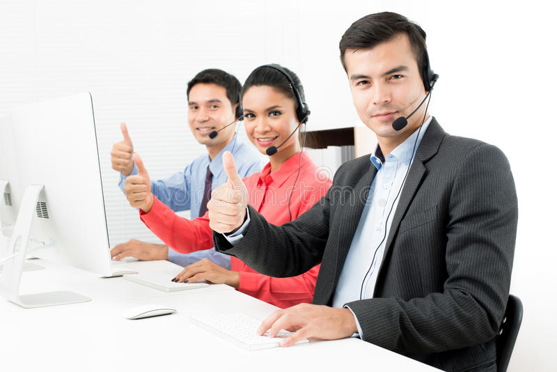 Call center or telemarketer team giving thumbs up stock images