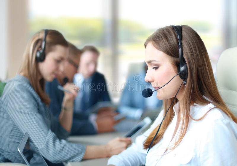 Call center worker. Portrait of call center worker accompanied by her team. Smiling customer support operator at work stock image
