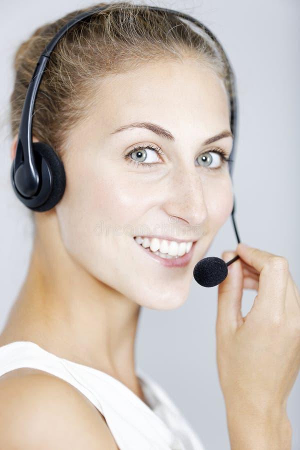 Call centerkvinna med hörlurar med mikrofon royaltyfri foto
