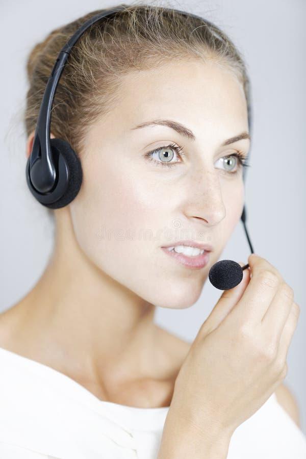 Call centerkvinna med hörlurar med mikrofon arkivfoton