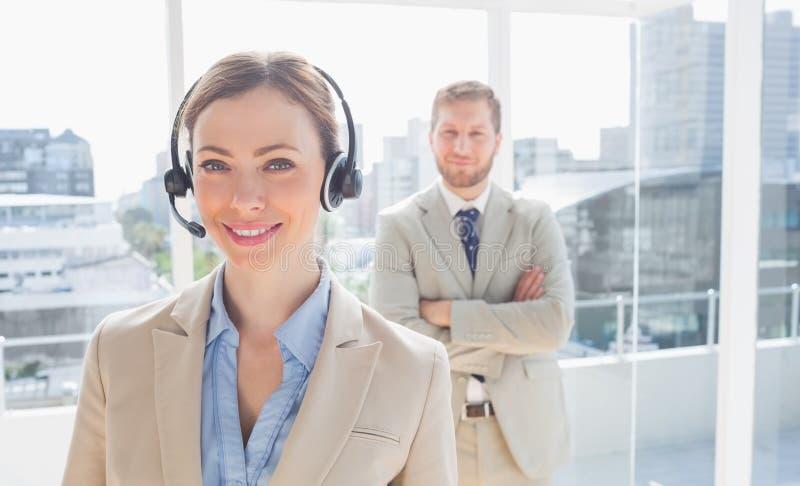 Call centermedelanseende med kollegan bak henne arkivbild