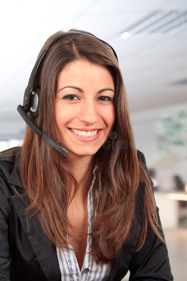 Call centre employee. Successful female call centre employee speaking over the headset stock photos