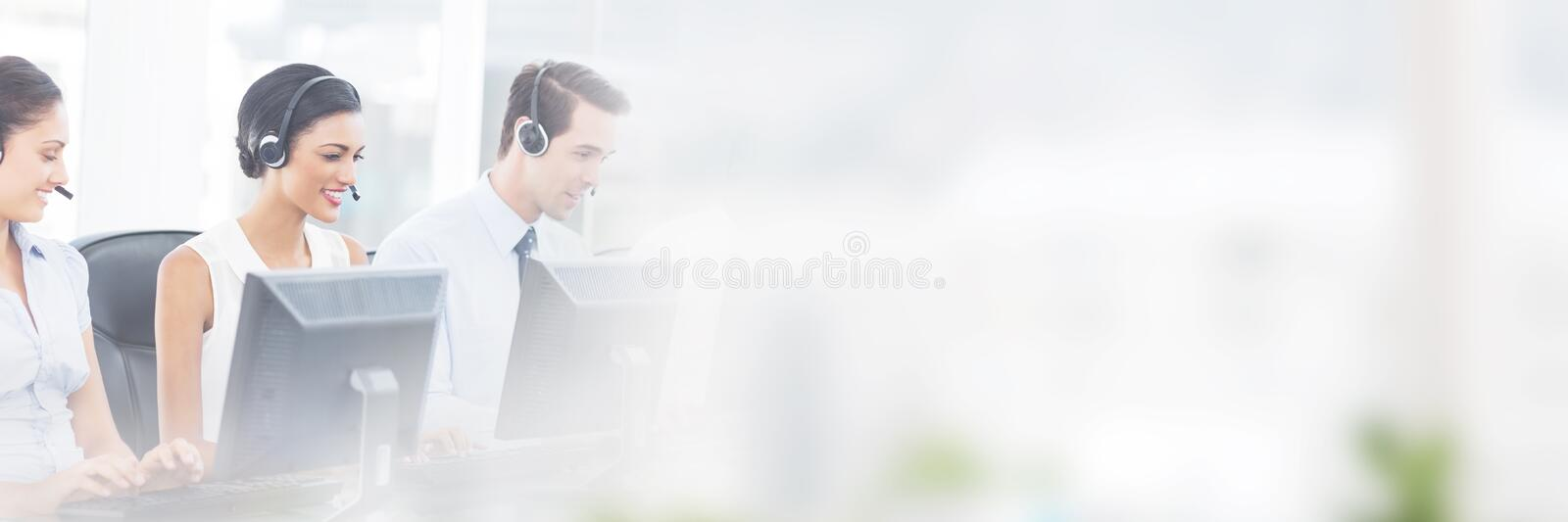 Call centre employees smiling while sitting royalty free stock images