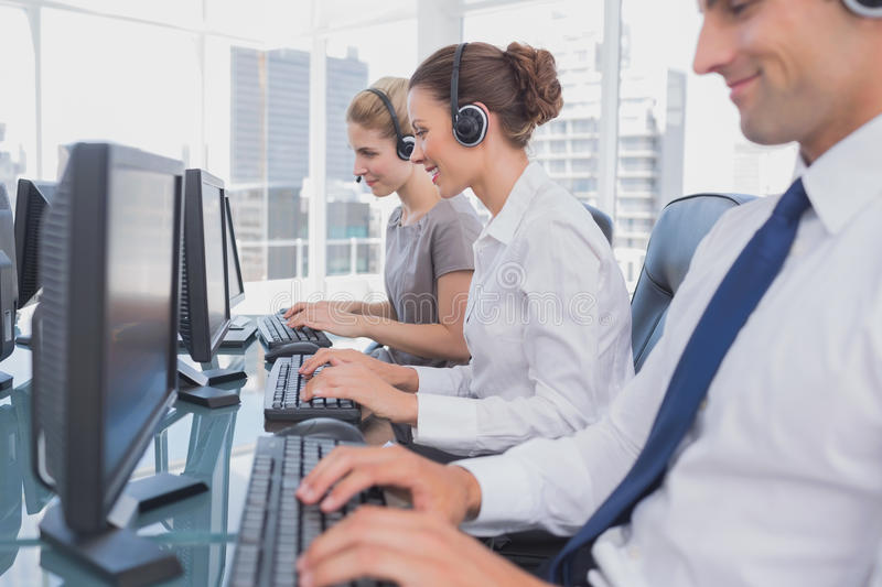 Call centre employees at work. On computer in office royalty free stock photo