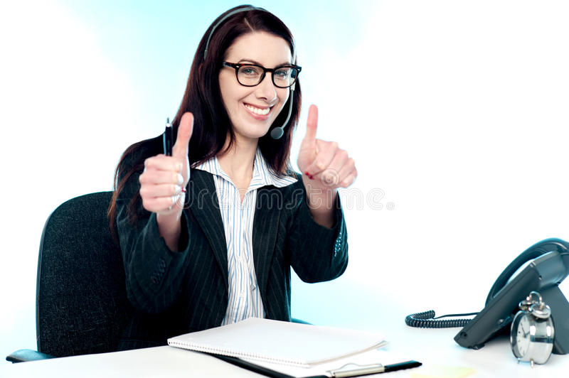 Call centre operator gesturing double thumbs up. Cheerful female call centre operator gesturing double thumbs up in joy stock image