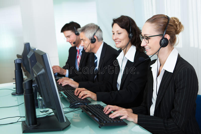 Call centre operators. Line of professional stylish call centre operators wearing headsets seated behind their computers giving assistance stock images