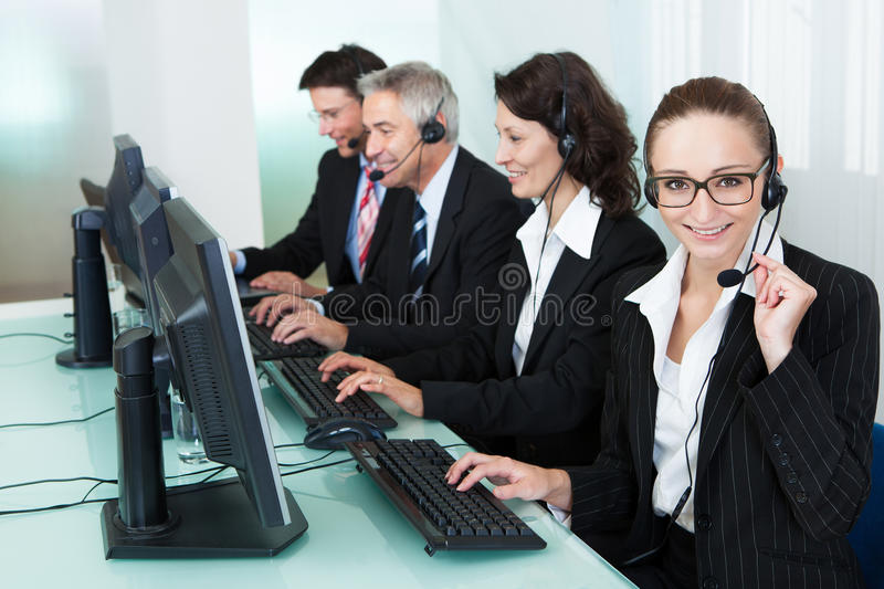 Call centre operators. Line of professional stylish call centre operators wearing headsets seated behind their computers giving assistance stock photos