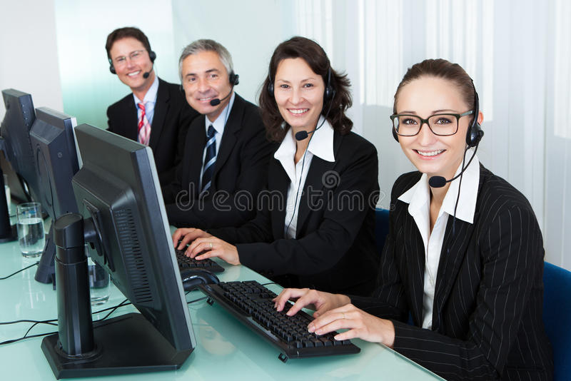 Call centre operators. Line of professional stylish call centre operators wearing headsets seated behind their computers giving assistance royalty free stock photos
