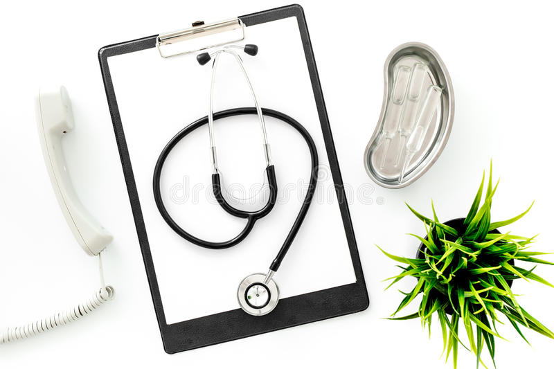 Call doctor. Phone, clip pad, stethoscope and cuvette with ampoulie on white background top view. Call doctor. Phone, clip pad and cuvette with ampoulie on white stock photography