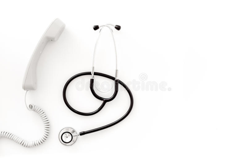 Call doctor. Phone and with stethoscope on white background top view copyspace. Call doctor. Phone and with stethoscope on white background top view stock image