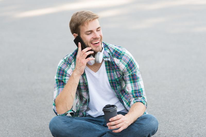 Call friend. Guy carefree student enjoy coffee outdoors. Life balance. Wellbeing and health. Having coffee break. Man. Sit on ground while drinking coffee stock photo