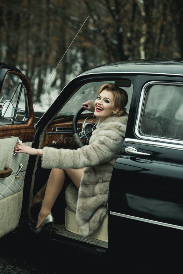 Call-girl dans la voiture de cru call-girl avec les cheveux élégants et le maquillage à la mode photo libre de droits