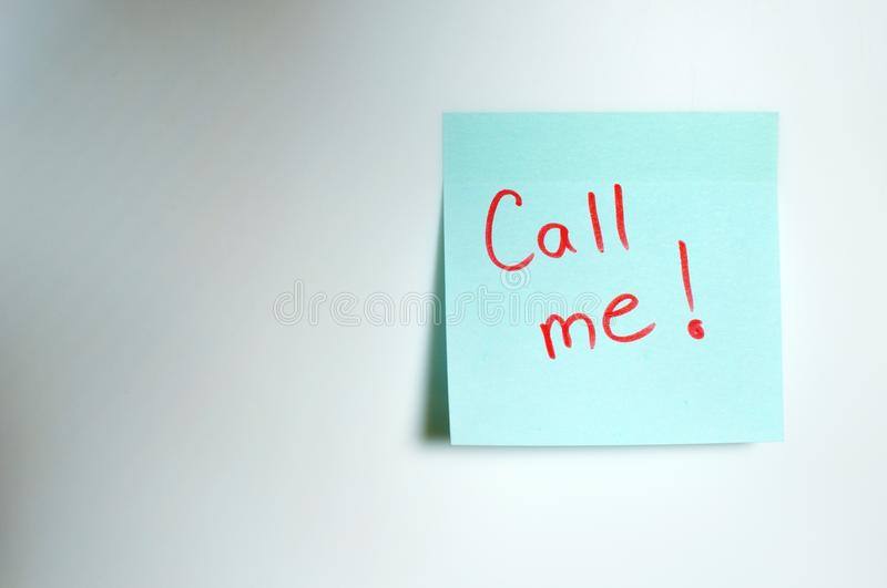 Call me written by hand and put on the white wall stock photos