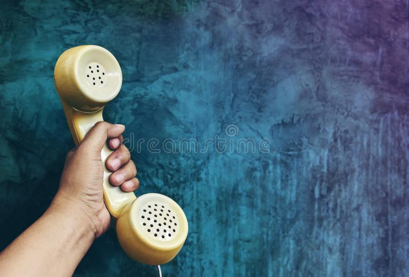 Call from the Past Concept, Hand Raise a headphone over Grunge C. Oncrete Cement wall, Vintage Retro color tone royalty free stock photo