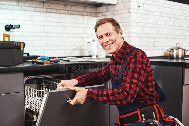 Call the professional. Male technician sitting near dishwasher and smiling royalty free stock photos