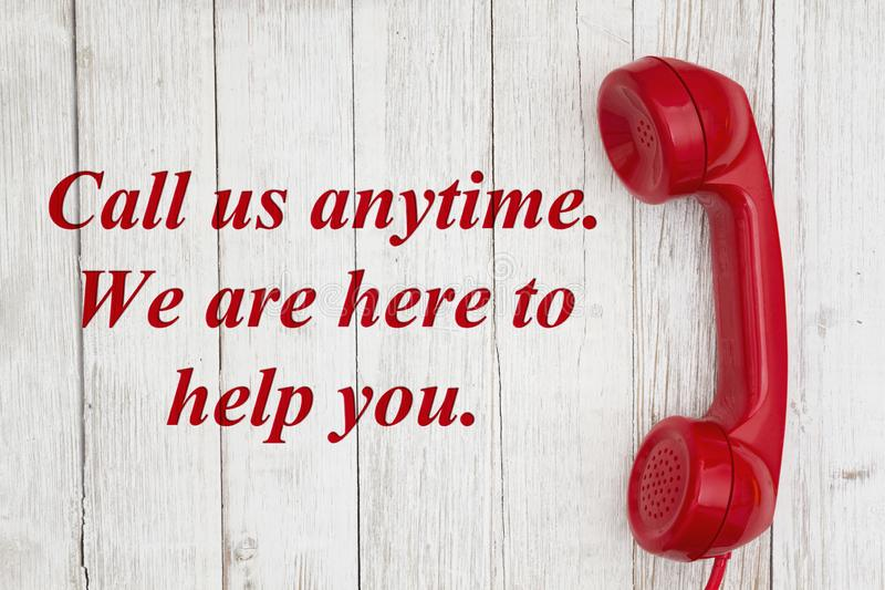 Call us anytime we are here to help text with retro red phone handset. On weathered whitewash textured wood royalty free illustration