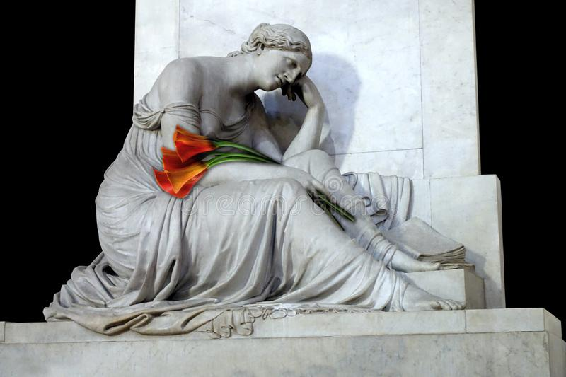 Calla Lilies and Marble Sculpture. A classic white marble sculpture of a woman in mourning commemorates a tomb in Florence, Italy. She holds a bouquet of orange royalty free stock image