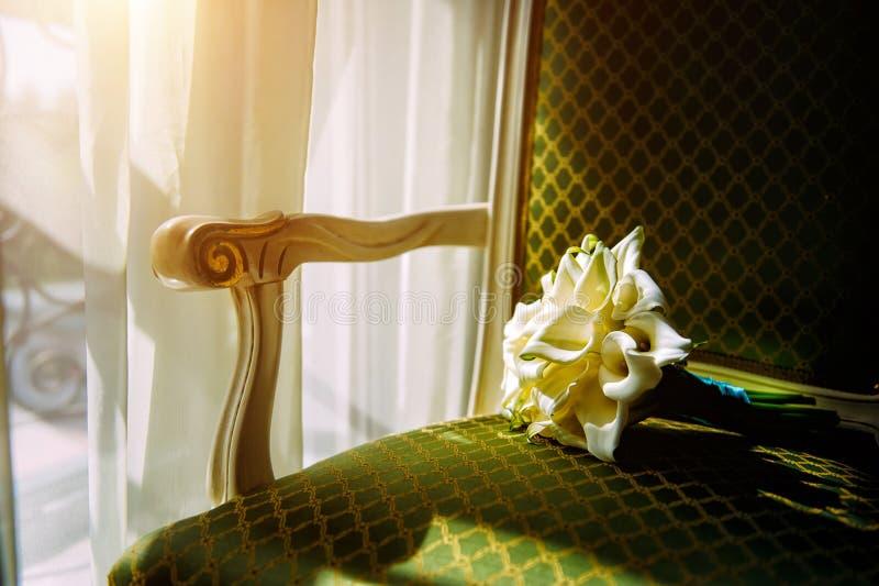 Calla, piękny bukiet dla panny młodej Wedding bouquet on a chair in sunlight, close-up fotografia royalty free