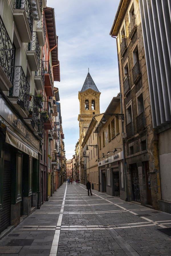 Calle圣阿古斯丁,圣阿古斯丁街在潘普洛纳,有圣奥斯丁教会塔的西班牙在背景中 库存照片