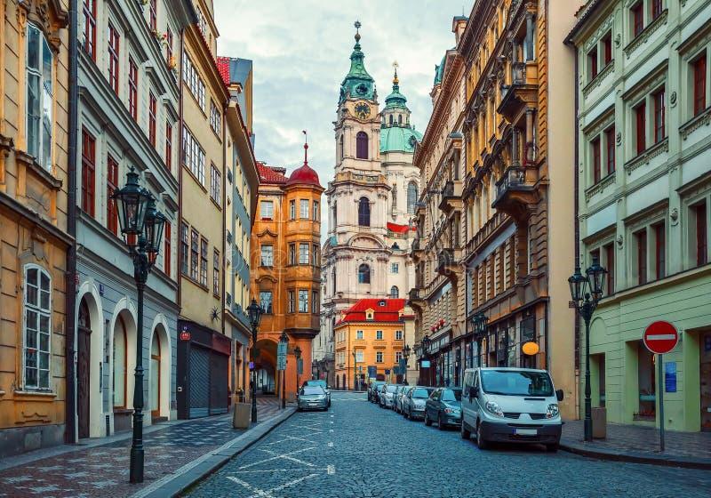Calle abandonada con la casa vieja y opinión sobre torre de la catedral en Praga fotos de archivo