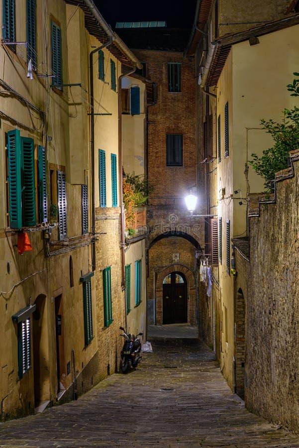 Calle acogedora estrecha medieval en Siena en la noche, Toscana imagen de archivo libre de regalías