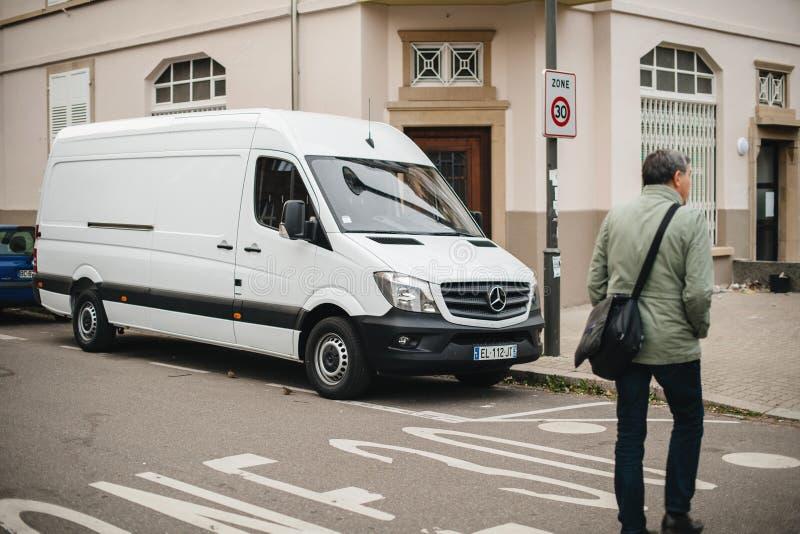 Calle adulta de la traves?a del hombre delante de la furgoneta blanca de Mercedes-Benz Sprinter imagenes de archivo