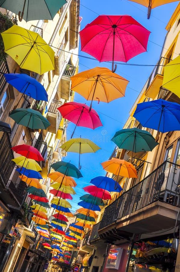 Calle antigua adornada con los paraguas coloridos imagenes de archivo