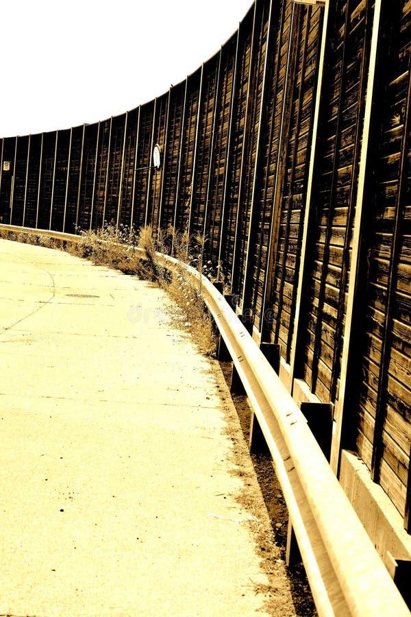 Calle cercada con la pared y el gardrail de madera imagenes de archivo
