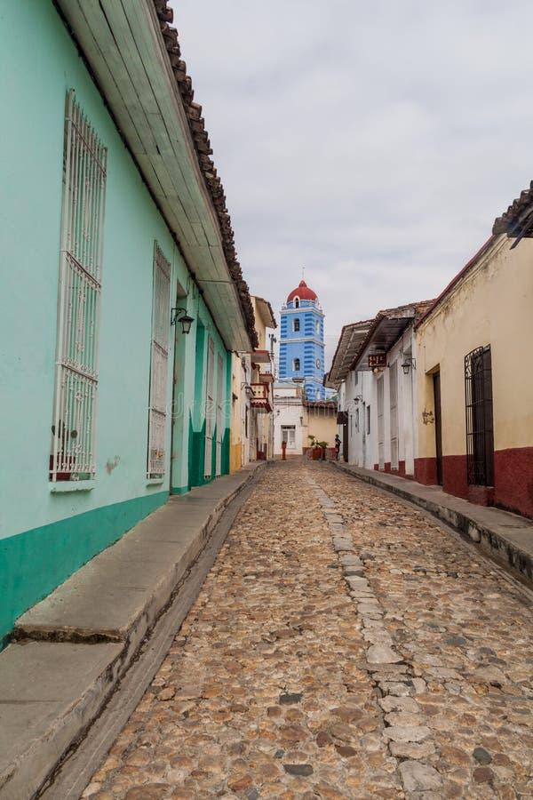 Calle Cobbled en Sancti Spiritus, Cuba La iglesia del alcalde de Parroquial en el backgroun foto de archivo